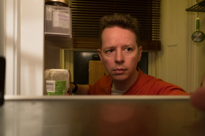 Simon taking photos of himself from the fridge